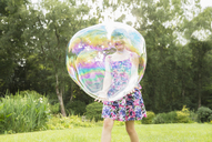 Father and daughter playing with large bubbles in backyard - CAIF18105