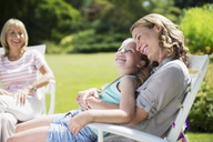 Mother and daughter relaxing in backyard - CAIF18108