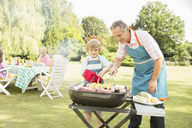 Grandfather and grandson grilling meat and corn on barbecue - CAIF18132