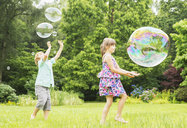 Children playing with bubbles outdoors - CAIF18135