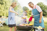 Multi-generation family standing at barbecue in backyard - CAIF18141
