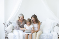 Multi-generation women using digital tablet on daybed - CAIF18249