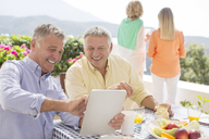 Senior men using digital tablet at patio table - CAIF18276