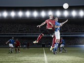 Soccer players jumping for ball on field - CAIF18327