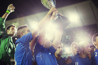 Soccer team celebrating with trophy on field - CAIF18339