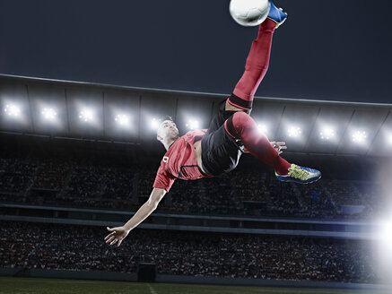 Soccer player kicking ball in mid-air on field - CAIF18369