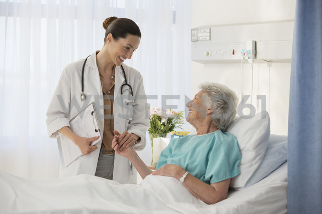 Doctor and senior patient talking in hospital room - CAIF18532