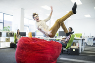 Businessman jumping into beanbag chair in office - CAIF18625