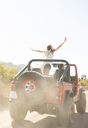 Woman cheering in sport utility vehicle on dirt road - CAIF18664