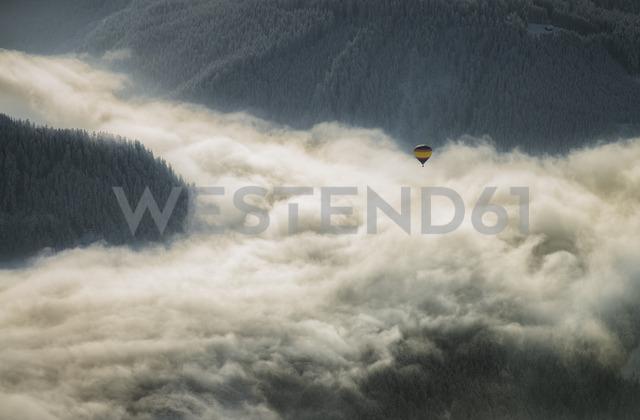 Austria, Salzkammergut, Hot air balloon over clouds in alpine landscape - STCF00411