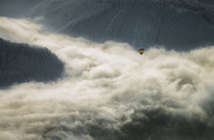 Austria, Salzkammergut, Hot air balloon over clouds in alpine landscape - STCF00411