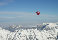 Austria, Salzkammergut, Hot air balloon over alpine landscape in winter - STCF00414
