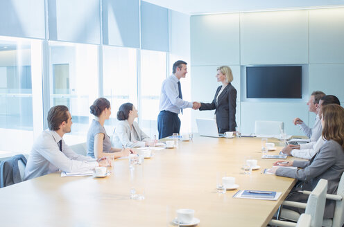 Business people shaking hands in meeting - CAIF18723