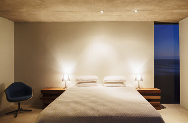 Illuminated lamps and bed in modern bedroom - CAIF18781