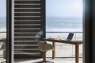 Desk and chair in modern home office overlooking ocean - CAIF18790