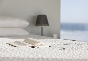 Book and glasses on bed in modern bedroom with ocean view - CAIF18811