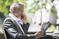 Businessman reading magazine at sidewalk cafe - CAIF18832