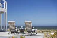 Lounge chairs on patio overlooking ocean - CAIF18850