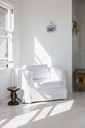 Sun shining on white armchair in corner - CAIF18859