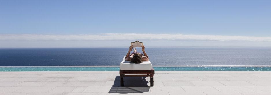 Woman relaxing on lounge chair at poolside overlooking ocean - CAIF18979