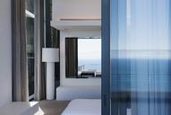 Glass door and windows of modern house overlooking ocean - CAIF18982