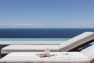 Lounge chairs on balcony overlooking ocean - CAIF19000