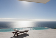 Lounge chair and infinity pool overlooking ocean - CAIF19009