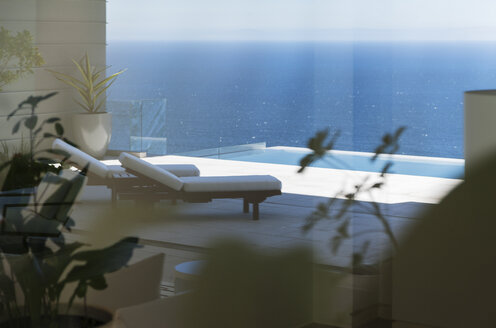 Lounge chairs and infinity pool overlooking ocean - CAIF19012