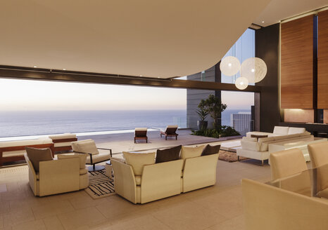 Living room in modern house overlooking ocean at sunset - CAIF19015