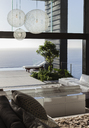 Sofas and tables in modern living room overlooking ocean - CAIF19018
