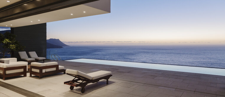 Modern patio and infinity pool overlooking ocean at sunset - CAIF19021
