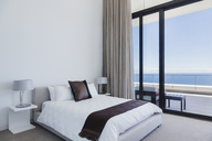 Bed and lamps in modern bedroom overlooking ocean - CAIF19036