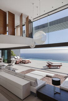 Living room in modern house overlooking ocean - CAIF19042