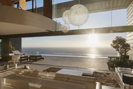 Modern living room overlooking ocean at sunset - CAIF19051