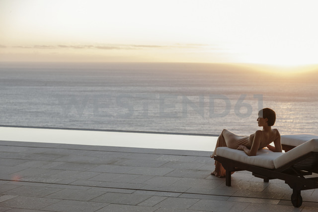 Woman in dress laying on lounge chair on patio overlooking ocean at sunset - CAIF19060