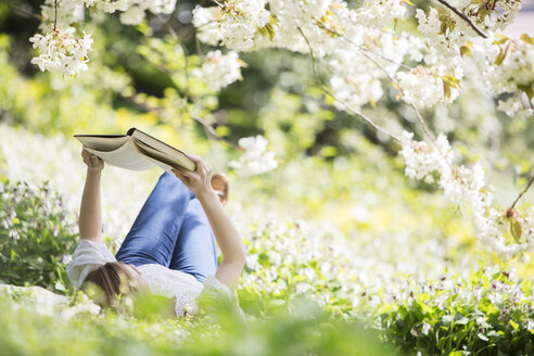 Woman reading book in grass under tree with white blossoms - CAIF19204