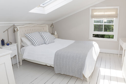 Bed in whitewashed attic bedroom - CAIF19240