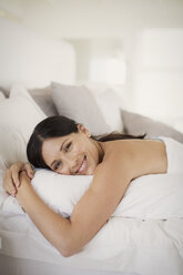 Woman hugging pillow on bed - CAIF19351