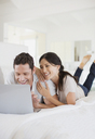 Couple using laptop on bed - CAIF19360