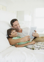 Father and son using digital tablet on bed - CAIF19375