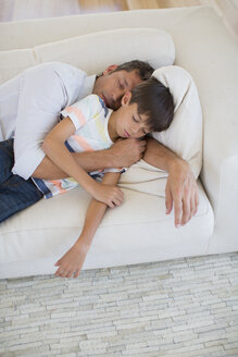 Father and son napping on sofa in living room - CAIF19378