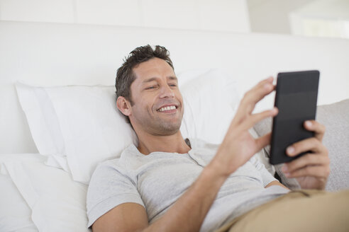 Man using digital tablet in bed - CAIF19381