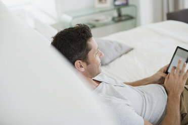 Man using digital tablet on bed - CAIF19390