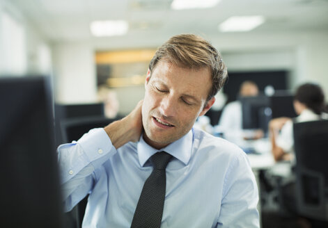 Businessman rubbing his neck in office - CAIF19417