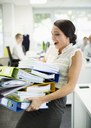 Businesswoman carrying folders in office - CAIF19426