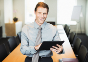 Businessman using digital tablet in office - CAIF19432