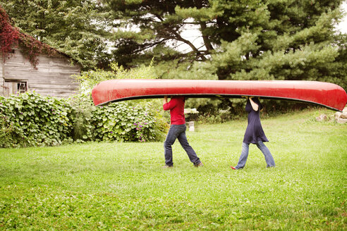 Side view of couple carrying boat on grassy field - CAVF09532
