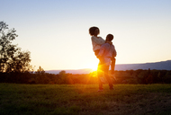 Man carrying woman on grassy field during sunset - CAVF09565