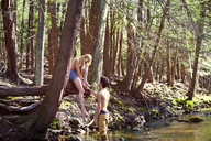 Man holding hand of girlfriend while standing in stream - CAVF09715