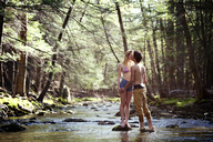 Couple kissing while standing on rocks in stream - CAVF09718